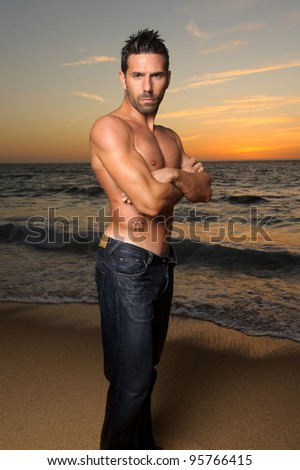 beautiful young man at sunset at the beach standing - stock photo