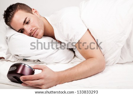 beautiful young man lying in bed looking at clock - stock photo