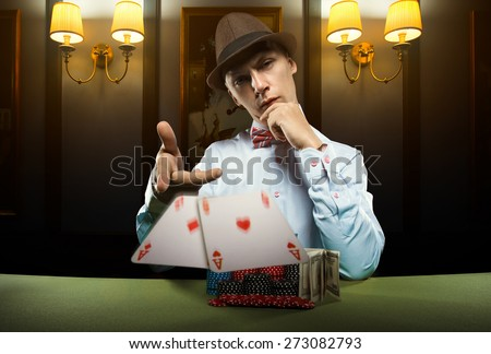 Beautiful young man on a beautiful background playing poker. Good luck in card games on the big money. Looking at the camera - stock photo
