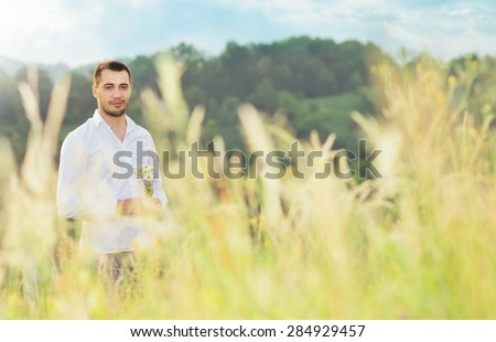 Beautiful young man standing in a grass in white shirt holding flowers, outdoors. Male beauty natural concept with copyspace for text. Seducer - stock photo