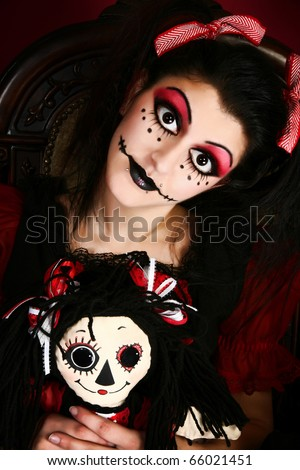 Beautiful young middle eastern woman in goth doll costume holding small goth doll. - stock photo