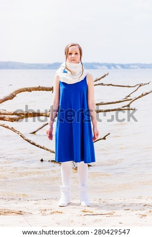 Beautiful young model in blue dress posing at summer beach near water - stock photo