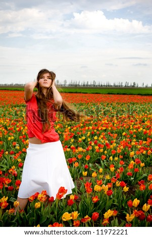 Beautiful young model in tulips field - stock photo