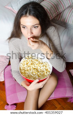 Beautiful young modern girl watching horror movie late at night. - stock photo