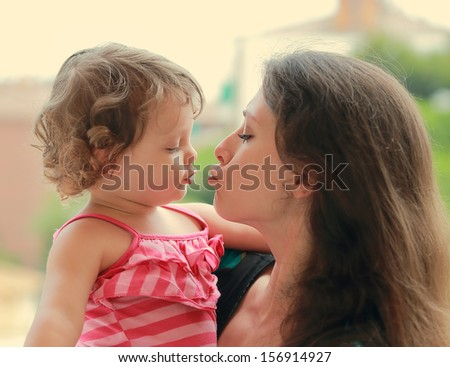 Beautiful young mother and baby girl going to kiss on nature background - stock photo