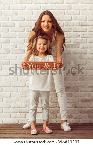 Beautiful young mother and her cute little daughter are holding a wooden plate, looking at camera and smiling, against white brick wall - stock photo