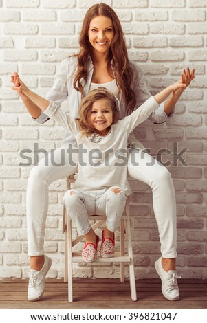Beautiful young mother and her cute little daughter are looking at camera and smiling, sitting against white brick wall - stock photo