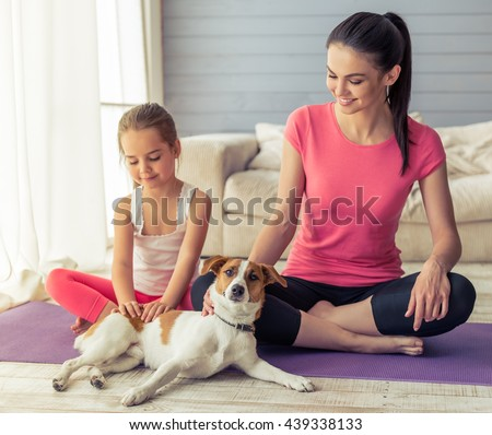 Beautiful young mother and her cute little daughter are patting their dog and smiling while sitting in lotus pose on yoga mat at home - stock photo