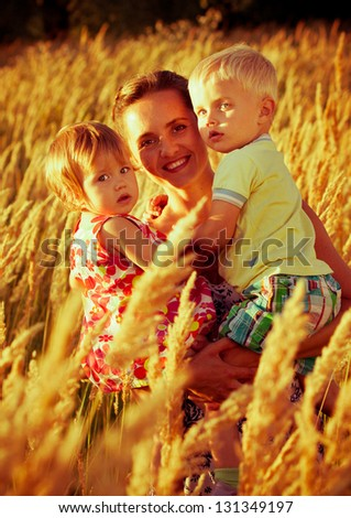 Beautiful young mother and her daughter and son at field on a sunny day - stock photo