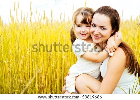 beautiful young mother and her daughter at the wheat field on a sunny day - stock photo