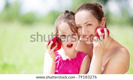 beautiful young mother and her daughter eating apples in the park on a sunny summer day - stock photo