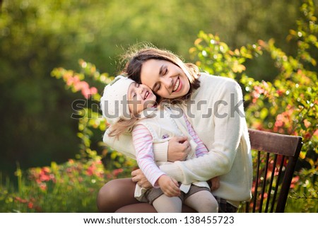 beautiful young mother and her daughter in the park - stock photo