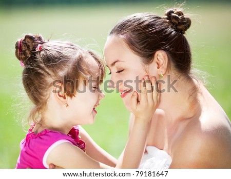 beautiful young mother and her daughter in the park on a sunny summer day  (focus on the woman) - stock photo