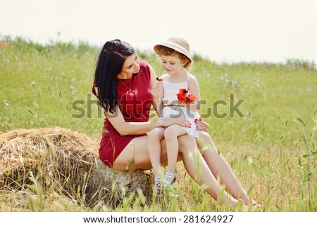 beautiful young mother and her daughter relaxing on grass  - stock photo