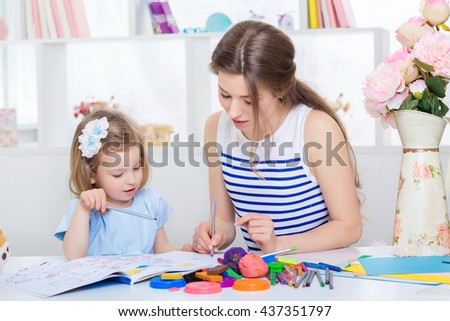 beautiful young mother and her little daughter drawing with pencils on the album. mother and daughter at home. - stock photo
