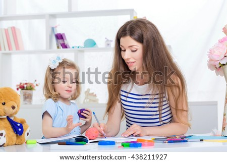 beautiful young mother and her little daughter  in blue dress drawing with crayons on the album. mother and daughter having fun at home. - stock photo
