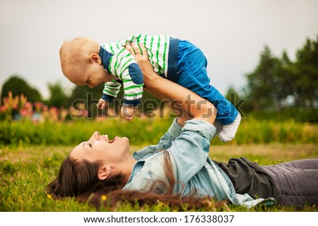Beautiful young mother and her son are having fun outdoors in sunshine - stock photo