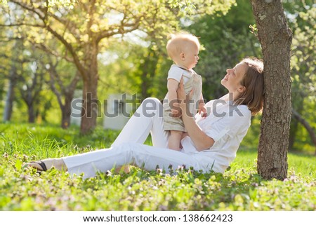 beautiful young mother and son  relaxing sitting grass background summer meadow green grass trees - stock photo