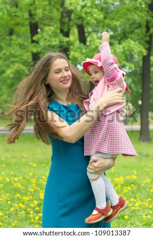 Beautiful young mother carrying little daughter in spring park - stock photo