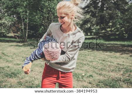 Beautiful young mother having fun and enjoying life with her daughter outdoors - stock photo