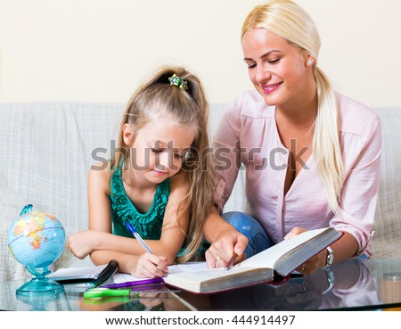 Beautiful young mother helping little girl to do homework - stock photo