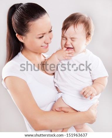 beautiful young mother holding a crying baby, against light studio background - stock photo