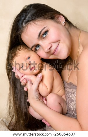 Beautiful young mother holding her seven days old newborn baby - stock photo