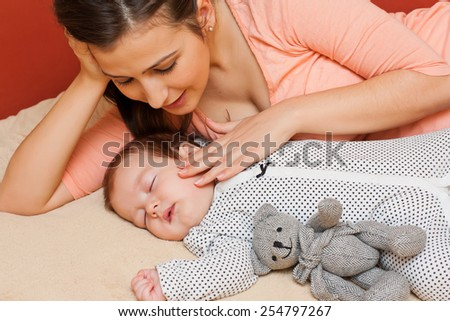 Beautiful young mother in bed with her sleeping baby. - stock photo