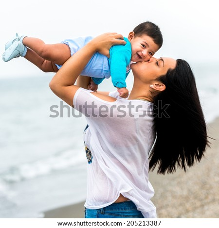 beautiful young mother playing with her baby boy on the beach on a summer day - stock photo