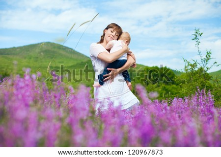 Beautiful young mother posing with a small child in her arms while standing in a field of purple flowers on the background of mountain and blue sky. Series. - stock photo