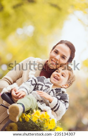 Beautiful young mother riding a bicykle with her little son sitting on the handlebars - stock photo