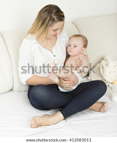 Beautiful young mother sitting on bed with her cute baby boy - stock photo