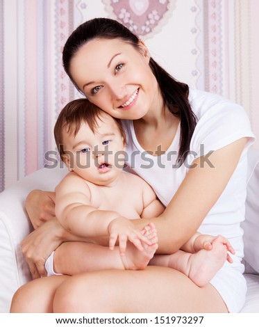 beautiful young mother sitting on the chair and holding her baby  - stock photo