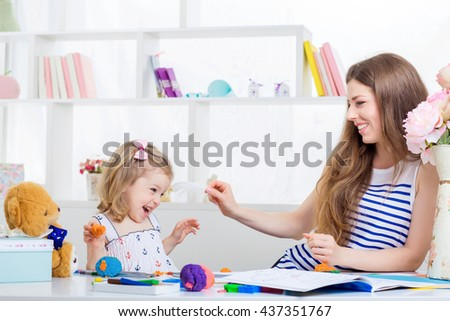 beautiful young mother  tickles her little daughter. mother and daughter having fun at home. - stock photo