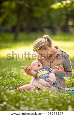 Beautiful young mother with adorable baby boy relaxing sitting on grass on background summer meadow. Summer outdoor portrait of happiness. mother with child in the park on the wild flowers meadow. - stock photo