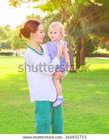 Beautiful young mother with cute little daughter on hands spending summer day in fresh green park, having fun outdoors, love and happiness concept - stock photo