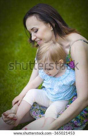 Beautiful young mother with daughter relaxing sitting on green grass background in summer park - stock photo