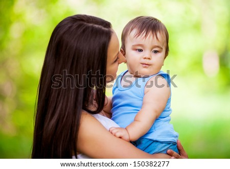 beautiful young mother with her baby in the summer park - stock photo