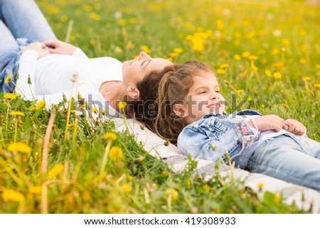 Beautiful young mother with her five years old daughter laying on the grass,and playing ,colored photo - stock photo