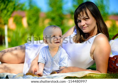 Beautiful young mother with her little son at park - stock photo