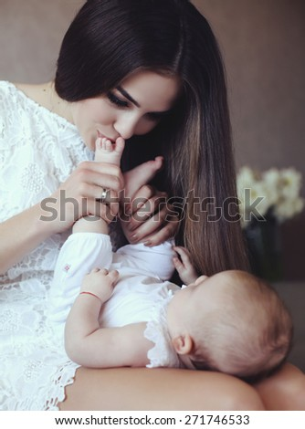 beautiful young mother with long dark hair posing with her little adorable baby - stock photo