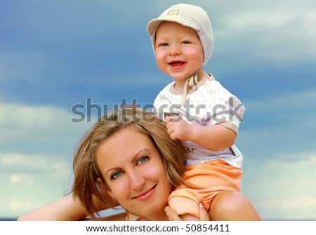beautiful young mother with son on the beach - stock photo