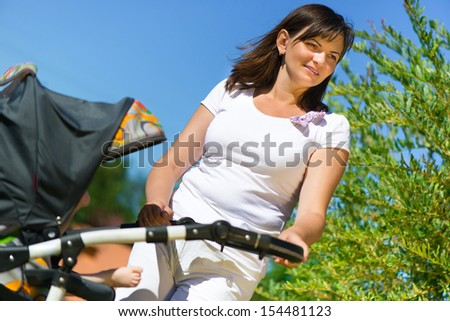 Beautiful young mother with stroller in summer park - stock photo