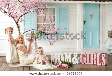 beautiful young mother with three daughters Happy family of mother with three daughters in stylish interior. Fashion style studio portrait.   - stock photo