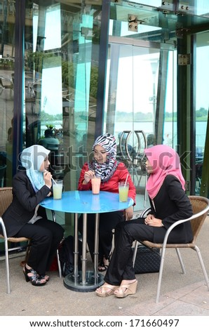 beautiful young muslim businesswoman sharing info together while drink at cafe - stock photo