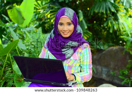 beautiful young Muslim girl sitting with notebook - stock photo