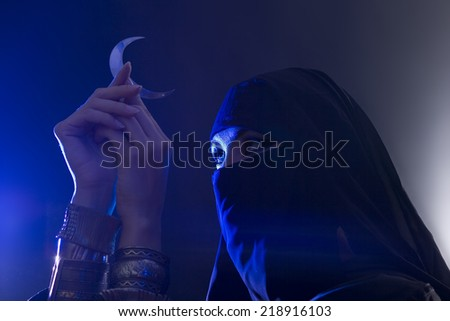 Beautiful young muslim girl with hijab and jewelry holding a moon symbol, spirituality - stock photo
