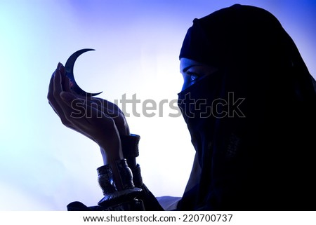Beautiful young muslim girl with hijab and jewelry holding a moon symbol, spirituality, Dark silhouette - stock photo