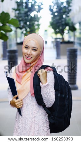 Beautiful young muslim student holding a file and backpack - stock photo