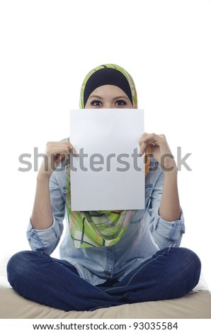 Beautiful young muslim woman seat and holding a blank paper.half face covered by blank paper - stock photo